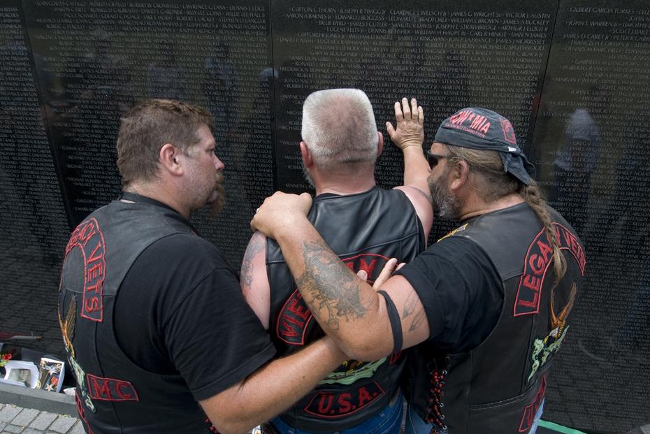 Two veterans of the Vietnam war comfort a comrade during his visit to the Vietnam Veteran's Memorial in Washington, D.C.