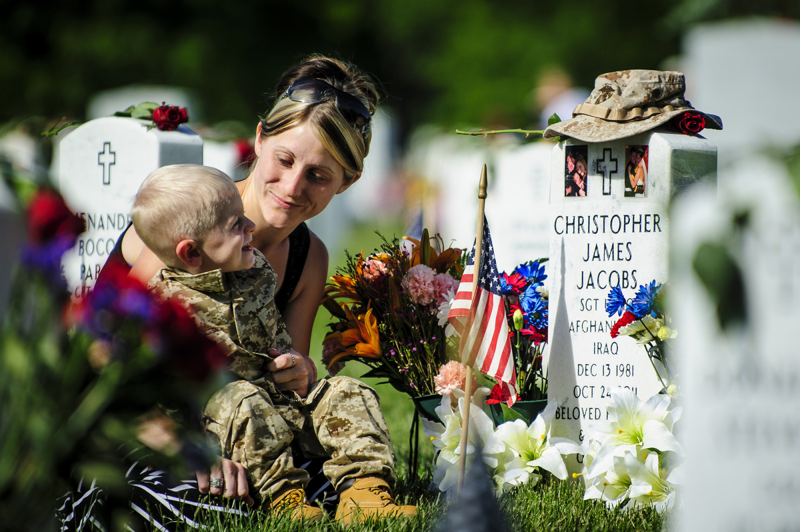 On Memorial Day, Brittany Jacobs of Hertford, North Carolina sits with her son, Christian, at the gravesite of her husband, Marine Sgt. Christopher Jacobs, at National Cemetery in Arlington Virginia, USA on 27 May, 2013. (Pete Marovich/ European PressPhoto Agency)
